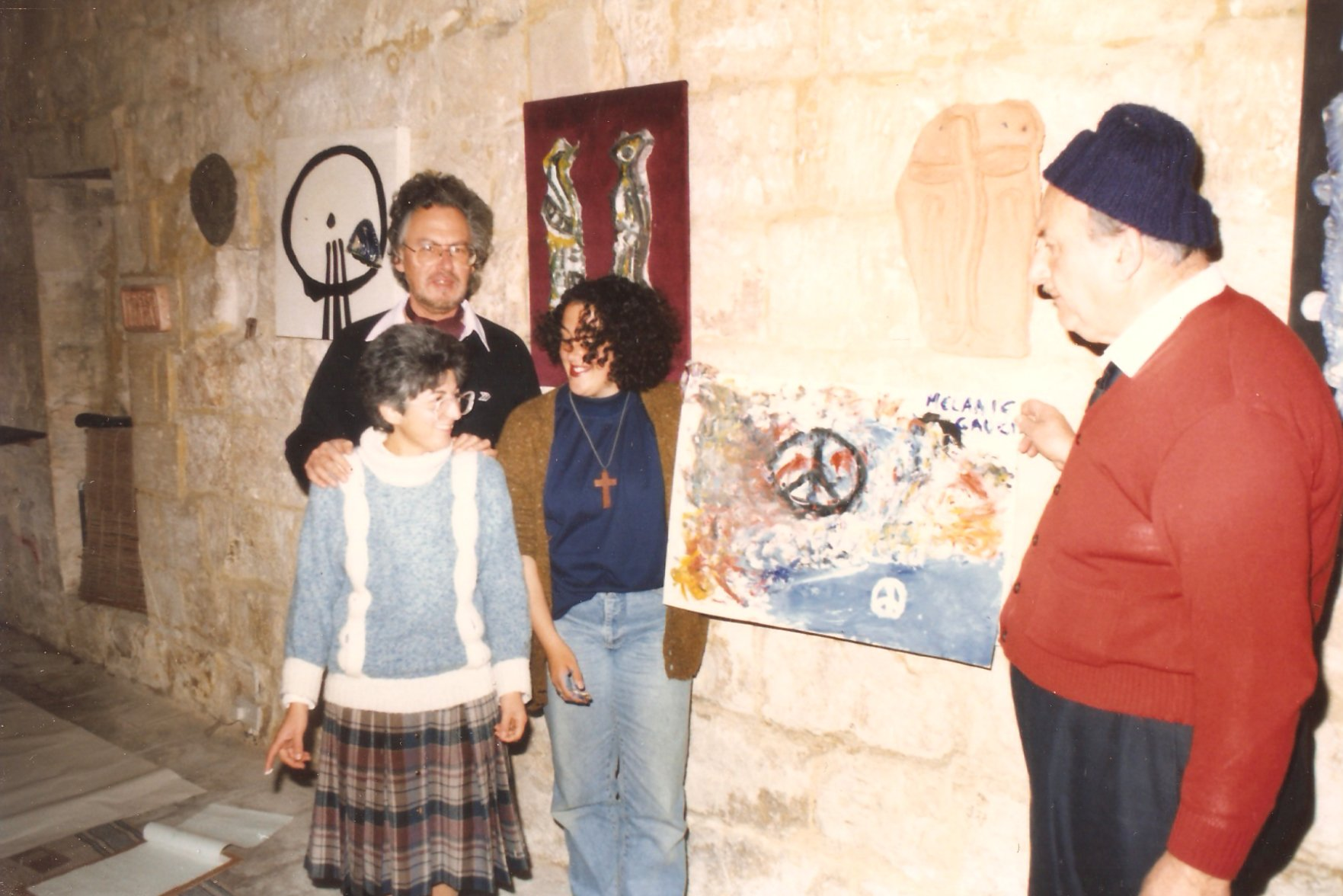 Photo of four people standing inside The Mill. Three are in a group on the left hand side of the photo, these are Richard England and Mary Rose Caruana and another woman. The Woman is holding a painting with peace symbols, the painting is held by Gabriel Caruana who is on the right hand side of the Photo. The photo was taken during the Colour and Form for Peace happening at The Mill.