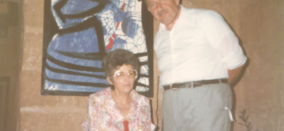 Photo of Mary Rose Caruana, sitting next to Gabriel Caruana on her left hand side, inside The mill - Art, Culture and Crafts Centre, with an abstract painting of Gabriel Caruana as a backdrop.