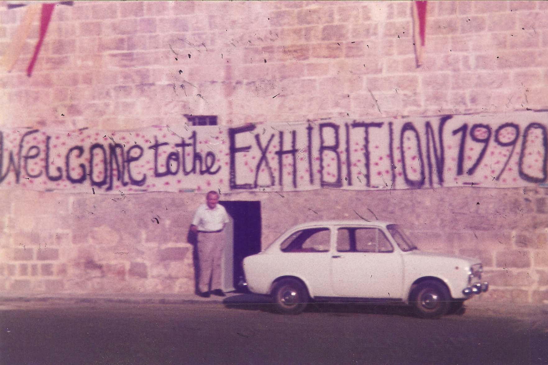 Photo showing the front of the Mill, with a large banner with the words 'Welcome to the Exhibition 1990' written on it. Gabriel Caruana stands below the banner next to the door. A white car is parked adjacent.